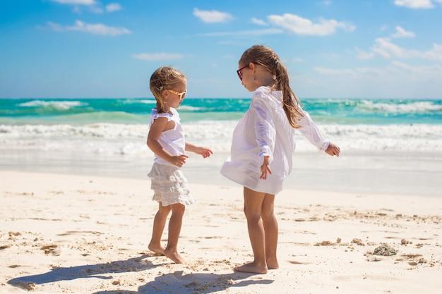 熱帯のメキシコのビーチで白い服を着た2人の妹が楽しい