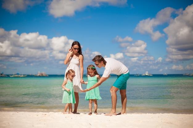 熱帯のビーチを歩いて2人の子供を持つ若い美しい家族