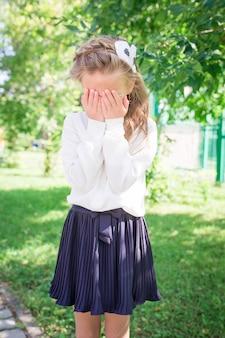 学校の前でポーズをとる2つのかわいい笑顔の女の子。