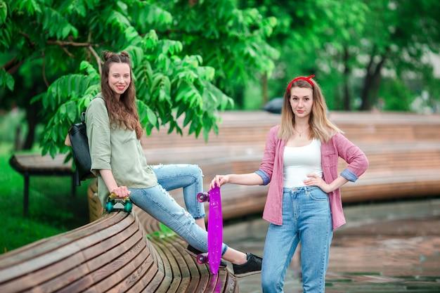 屋外の公園でスケートボードを持つ2つの内気な少女。スケート公園で一緒に楽しんでアクティブなスポーティな女性。