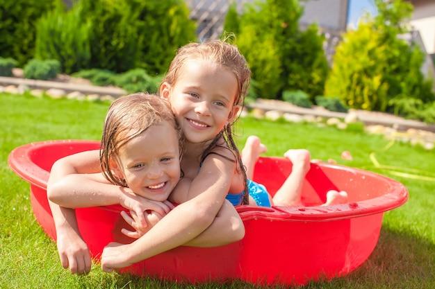 暑い晴れた日にプールで遊んで、水しぶきの2人の妹