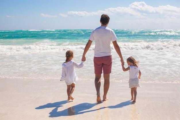 父と白い砂浜の上を歩く彼の2人のかわいい娘の背面図