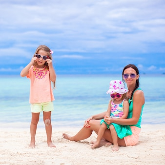 晴れた日にエキゾチックなビーチで若い母親と2人の愛らしい娘