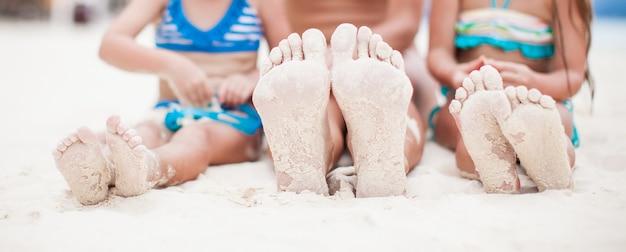 白い砂浜で母と2人の娘の足のクローズアップ