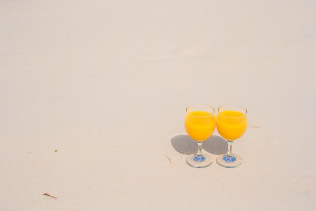 熱帯の白いビーチにオレンジジュースを2杯