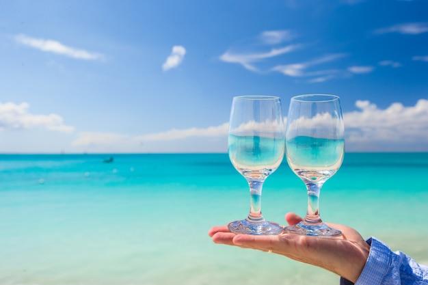 ターコイズブルーの海の背景に2つのきれいなメガネ