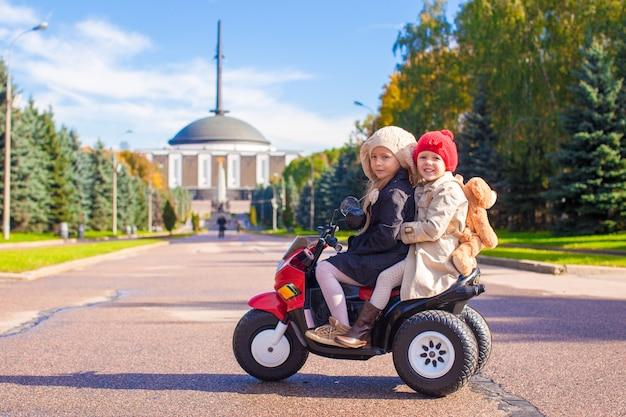 大きな公園でおもちゃのバイクに座っている2つの小さな美しい姉妹
