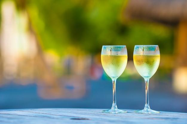 木製のテーブルに日没でおいしい白ワインを2杯