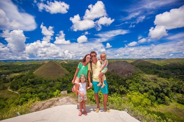 ボホール島のチョコレートヒルズの背景に2人の女の子と若い家族