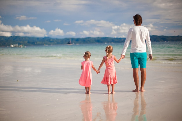 父と海沿いを歩く2人の小さな娘の背面図