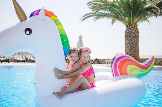 スイミングプールで遊ぶ2つの小さな子供たち