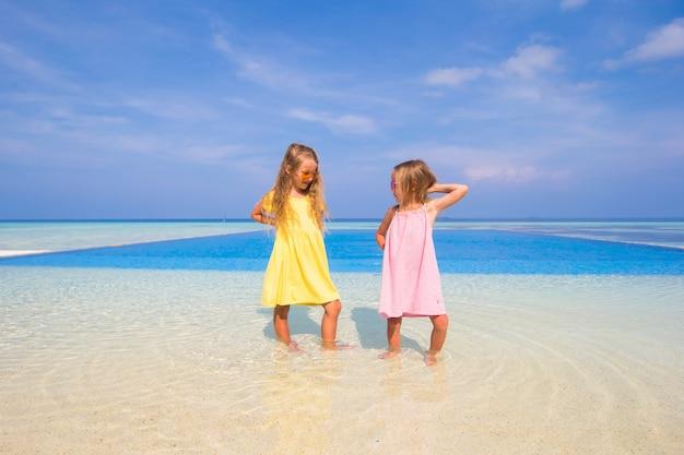 プールの近くで2人のかわいい妹が一緒に楽しんでいます