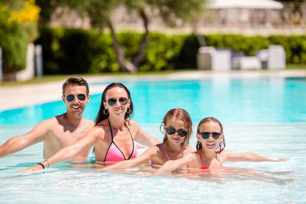 2人の子供を持つ若い家族は、屋外プールで夏休みを楽しむ