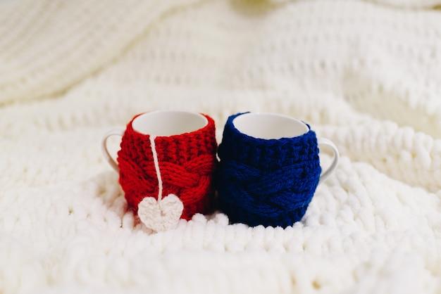 バレンタインデーの毛布に分離された暖かいウールに包まれた青と赤の2つのカップ