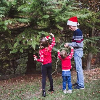 赤いクリスマス帽子の父と休日前に家の庭で屋外のクリスマスツリーを飾る赤いセーターの2人の娘
