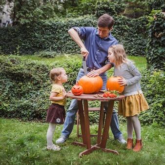 父と2人の娘がハロウィーンのカボチャを彫刻