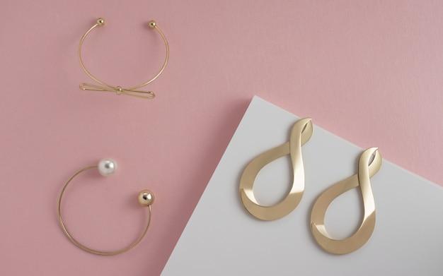 ピンクと白のパステルカラーの壁に2つのゴールデンブレスレットとモダンなイヤリングペアのトップビュー