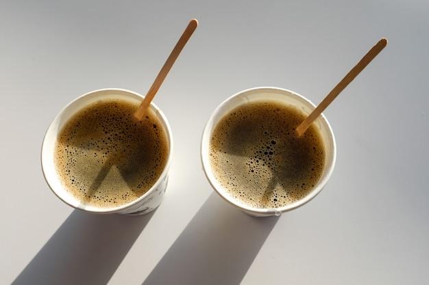 2 бумажных стакана с коробками лежат на столе в кафе. кофе с собой. утро.