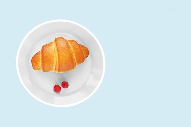 クロワッサンと青の背景に白い皿の上の2つのラズベリーの果実