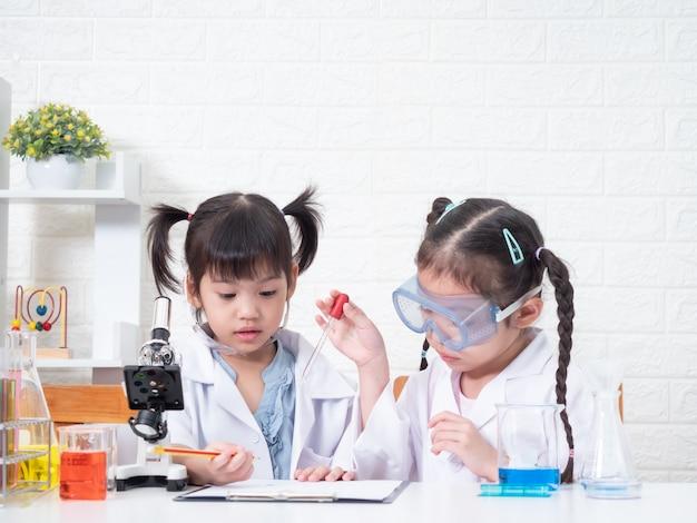 Маленькая азиатская роль девушки отпрыска 2 играя ученого в научной лаборатории с оборудованием. обучение и воспитание малыша.