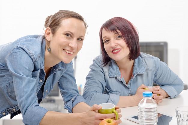 2人の女性の同僚がコーヒーブレークを作っています。