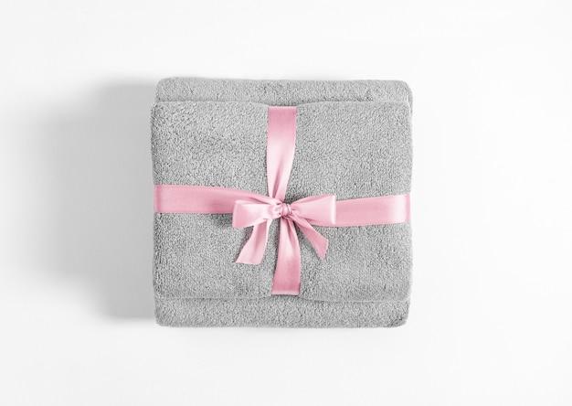 分離されたピンクのリボンで結ばれた2つの折られたテリータオル。白い背景に対して灰色のテリー織りのタオルのスタック。