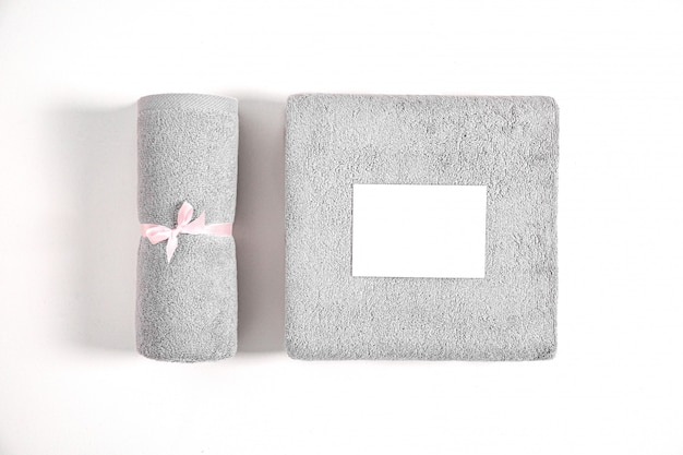分離されたピンクのリボンで結ばれた2つの巻き畳まれたテリータオル。白い背景に対して白い空漫画カードと灰色のテリー織りのタオルのスタック。上面図。
