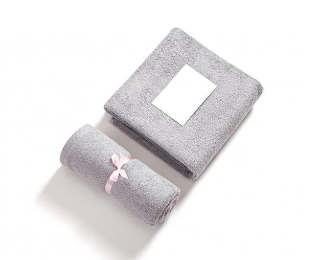 分離されたピンクのリボンで結ばれた2つの巻き畳まれたテリータオル。白い背景に対して白い空漫画カードと灰色のテリー織りのタオルのスタック。