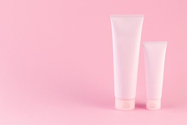 パステルピンクの背景に2つの化粧品のチューブパッケージ。