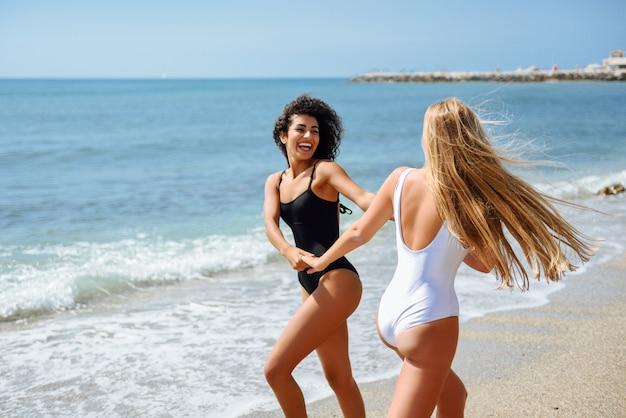 水泳の2人の若い女性がビーチで抱かれている。