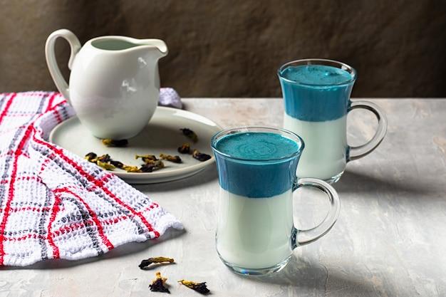 ブルーダルゴナ抹茶ブルーラテ2杯、ライトグレーのテーブルにエンドウ蝶からのクリーム色の飲み物