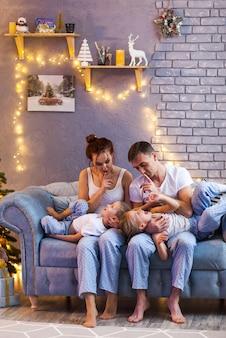 美しいリビングルームで2人の子供とクリスマス家族