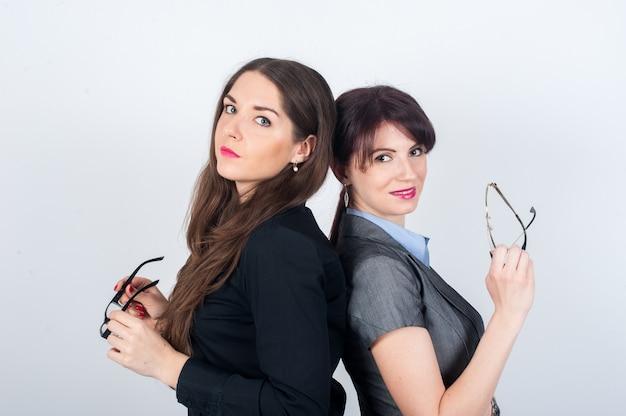 背中合わせに立っている2人のビジネス女性