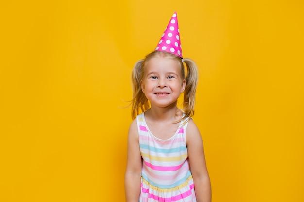色付きの黄色の背景にピンクの帽子の2つのポニーテールのお誕生日おめでとう子女の子。