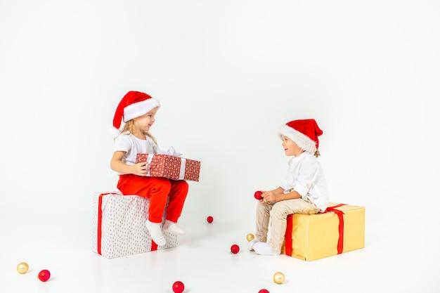 ギフトボックスの上に座ってサンタ帽子で2つの面白い小さな子供たち。白い壁に分離されました。クリスマスと新年のコンセプト。