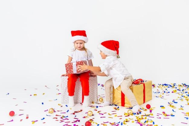 ギフトボックスの上に座ってサンタ帽子で2つの面白い小さな子供たち。白い壁、床に紙吹雪に分離されました。クリスマスと新年のコンセプト。
