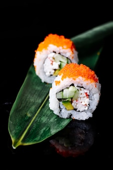 黒スペースの緑の葉の上に2本の寿司があります。