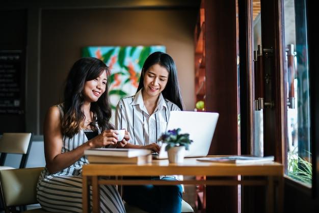 コーヒーショップカフェで一緒にすべてを話している2人の美しい女性