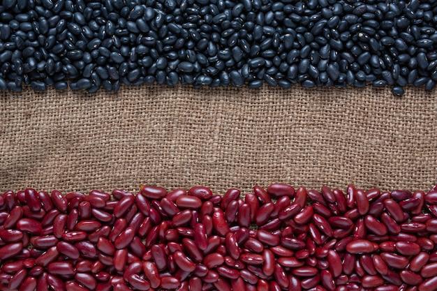 茶色の木の床に置かれた2色の豆の種。