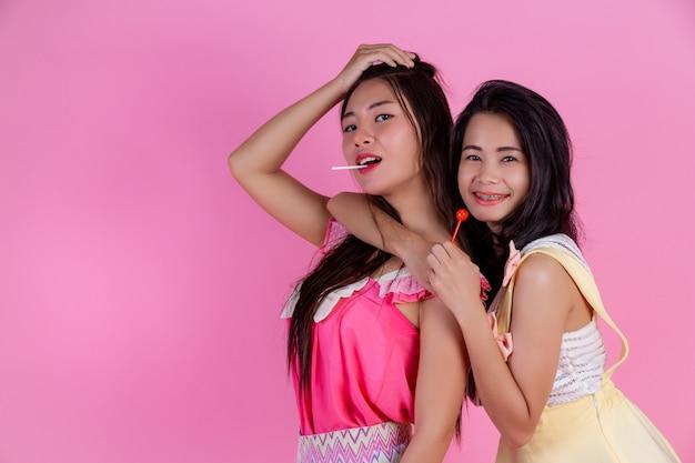 友達である2人のアジアの女の子は幸せでピンクをしています。