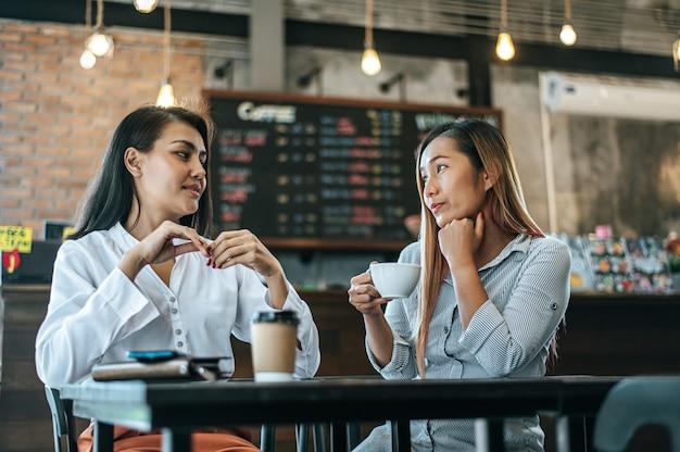 座って、コーヒーを飲みながら、カフェでおしゃべりする2人の女性