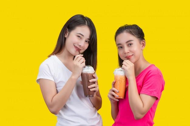 2 азиатских женщины выпивая замороженный чай молока и замороженное какао на желтом цвете.