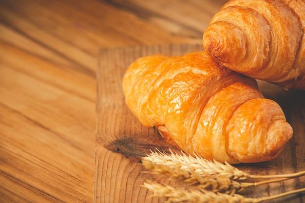 古い木の床に置かれたパンと大麦の2つのパン。
