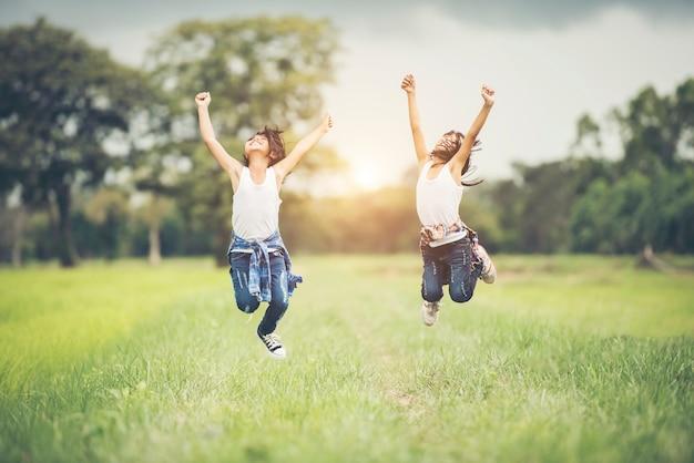 2人の少女が自然公園で幸せにジャンプ