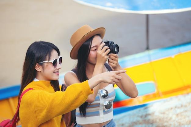 2人の女性観光客が場所を見つけるために地図を持っています。