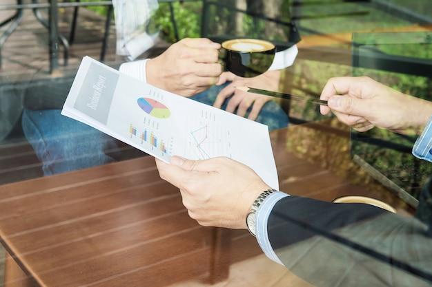 Бизнесмен 2 обсуждая их диаграмму в кофейне