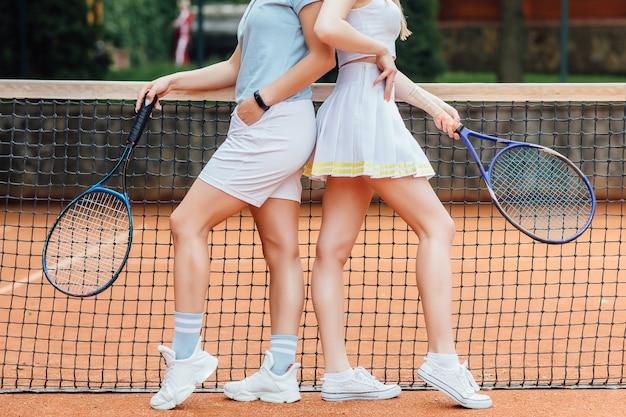 2人のテニスプレーヤーの女性がテニスコートを離れることは絶対にしないでください。