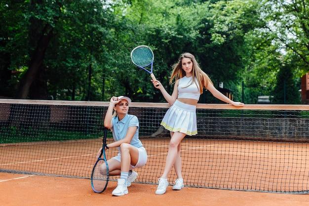 競技の準備ができてラケットを持つ2人のスポーティな女の子のテニスプレーヤーの写真。