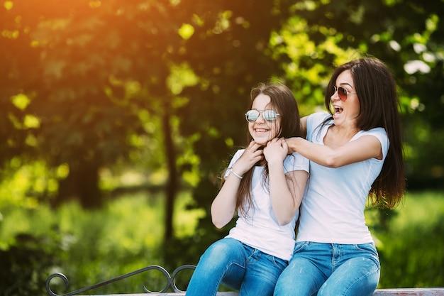 公園に座って楽しんでいる2人の女の子