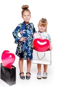 На фото 2 девочки в элегантных платьях держат большие сумки с воздушными шарами в форме сердечек внутри